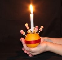 A hand holding a lit candle