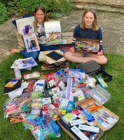 Two girls surrounded by sationery items