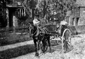 A man riding a horse drawn carriage