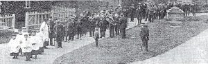 A vintage photo of a group of people standing in front of a crowd
