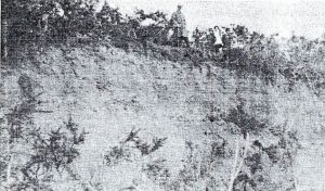 A group of people standing above a cliff